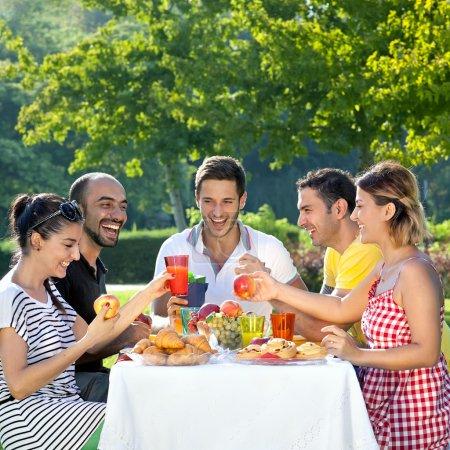 Foto de Multiétnicos amigos compartiendo una agradable comida sentada en una mesa al aire libre en el jardín riendo y bromeando juntos - Imagen libre de derechos