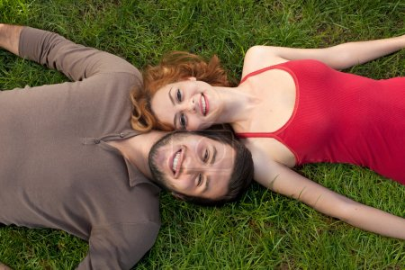 Happy couple in love laying down on the grass