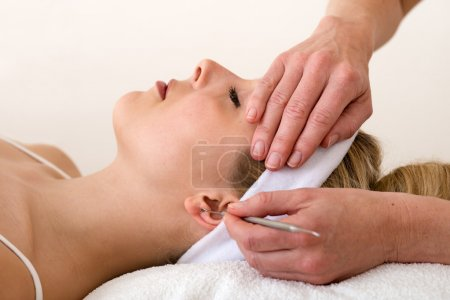 Chiropractor applying ear acupuncture techniques. ...