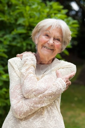 Elderly woman hugging herself with her arms in a garden