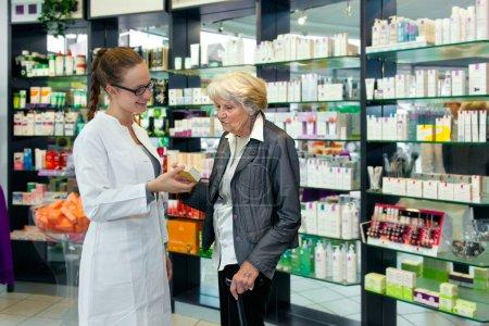 Pharmacist helping a senior lady