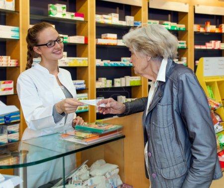 Smiling pharmacist serving a senior lady