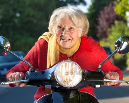 Senior woman speeding on a scooter bike