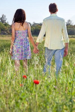 Photo for Affectionate young couple holding hands, closeup view from behind - Royalty Free Image