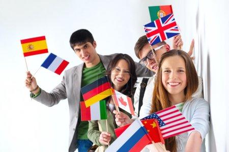 Photo pour Groupe de bonne humeur des étudiants heureux holding drapeaux internationaux et regardant la caméra s'appuyant sur un mur blanc au campus. concept de l'éducation internationale - image libre de droit