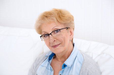 Portrait of an attractive elegant senior woman relaxing and drea