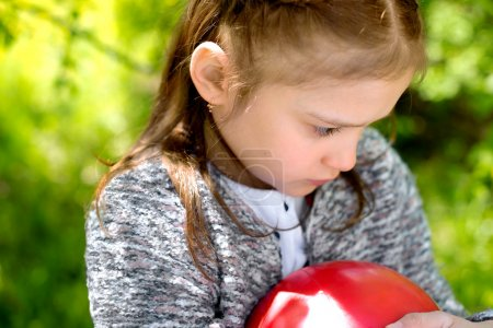 Outdoor portrait of sad little girl holding a red ball in her ha