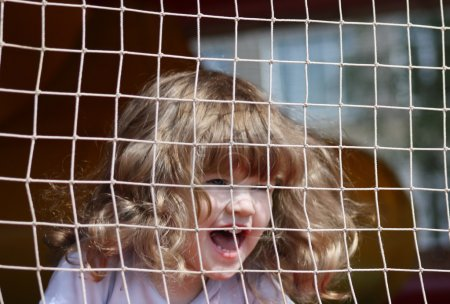 Little beautiful happy girl shouts in green playground with grid