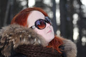 Happy girl in warm clothes and sunglasses looks away in forest a