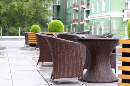 Wicker furniture in summer cafe on cinema terrace after rain