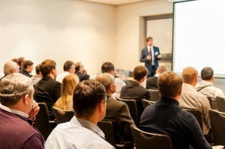 personas sentadas en la Conferencia de negocios y conferencista en la pantalla