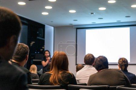 Photo pour Conférence d'affaires. personnes assises arrière et conférencier à l'écran - image libre de droit