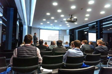 Photo pour Personnes assises arrière à la Conférence d'affaires et conférencier à l'écran blanc - image libre de droit