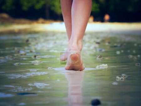 Photo for Girl walking on sand beach leaving footprints - Royalty Free Image
