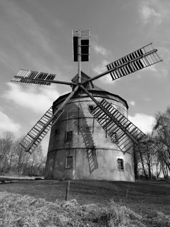 Renewal wind mill house into summer house. New red roof, repaired wind blades. Black and white photo.