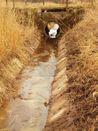 Photo pour Canal de drainage dégagé entre les prairies au printemps. Eau dans le drain, vieille herbe sèche sur les berges, pont caillouteux cassé . - image libre de droit