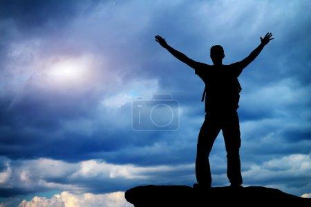 Foto de La silueta de un hombre en la cima de una montaña . - Imagen libre de derechos