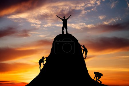 Photo for Man on top of the mountain and the other people to climb up on fiery orange background. Rock climber at sunset background. Sport and active life. - Royalty Free Image