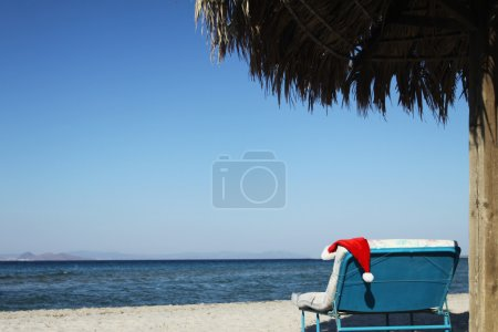 Santa Claus hat on beach under sunshade