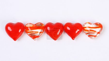 In row of five red and clear glass hearts
