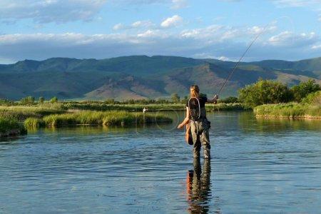 Photo pour Pêche à la mouche de la truite dans un ruisseau alimenté au printemps en Idaho - image libre de droit