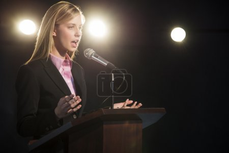 Young businesswoman giving speech at podium in aud...