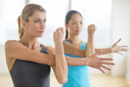 Women Looking Away While Doing Stretching Exercise