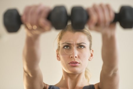Dedicated Woman Weightlifting At Health Club