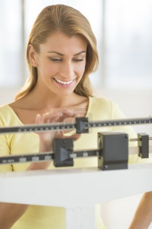 Happy Woman Weighing Herself On Balance Scale