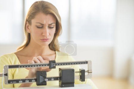 Photo for Young Caucasian woman using balance weight scale at gym - Royalty Free Image