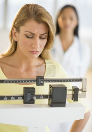 Woman Weighing Herself On Balance Weight Scale At Clinic