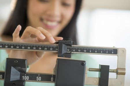Photo for Midsection of mid adult Asian woman smiling while adjusting balance weight scale - Royalty Free Image