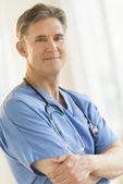 Jistý muž chirurg stojící zkřížil na prsou