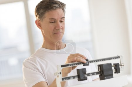 Man Weighing Himself On Balance Weight Scale