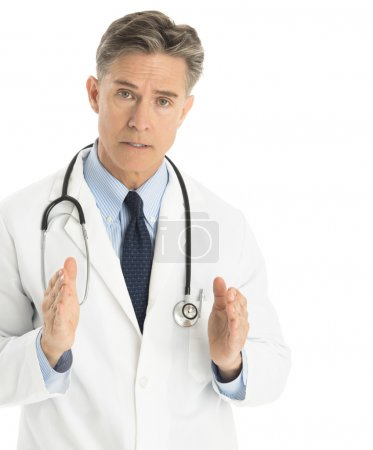 Serious Doctor Gesturing Against White Background