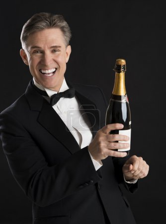 Cheerful Man In Tuxedo Holding Champagne Bottle