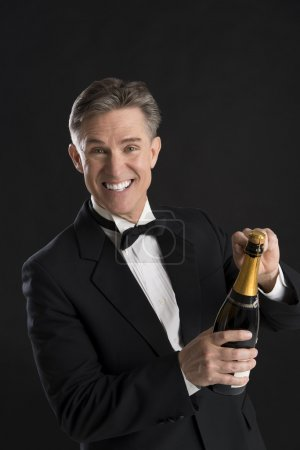 Portrait Of Cheerful Man In Tuxedo Opening Champagne Bottle