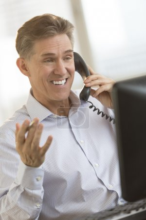 Happy Businessman Communicating On Telephone While Looking At Co