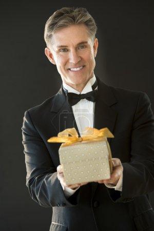 Portrait Of Happy Man In Tuxedo Giving Present
