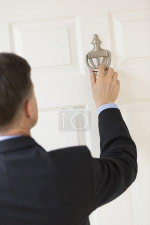 Businessman Knocking Door Handle