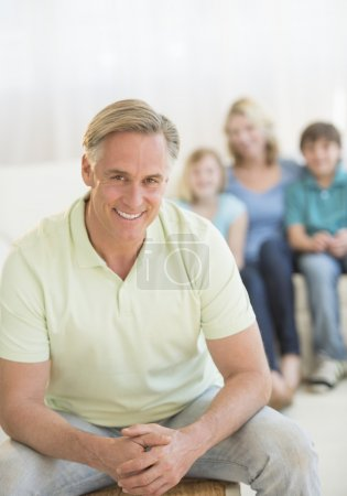 Happy Man With Family Sitting In Background At Home