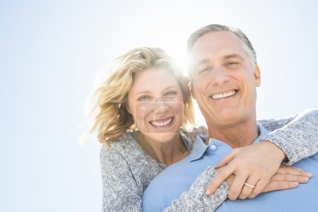 Photo for Low angle portrait of cheerful mature woman embracing man from behind against clear sky - Royalty Free Image