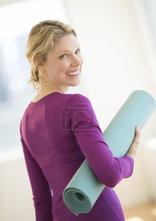 Woman With Rolled Up Exercise Mat In Gym