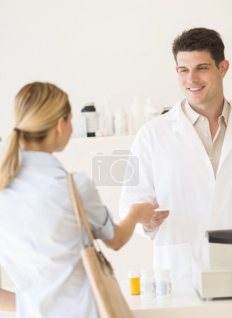 Customer Giving Prescription Paper To Pharmacist In Store