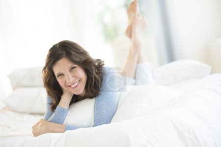 Photo for Portrait of cheerful mature woman lying in bed at home - Royalty Free Image