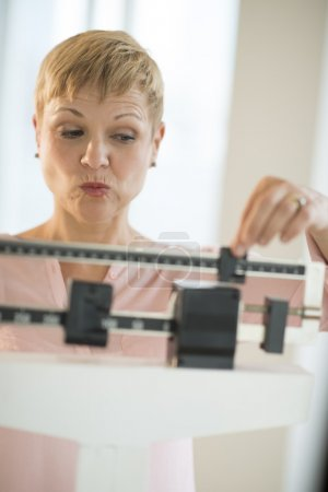 Mature Woman Adjusting Sliding Weight Scale