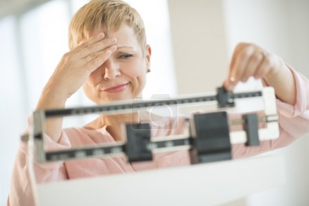 Doubtful Woman Adjusting Weight Scale