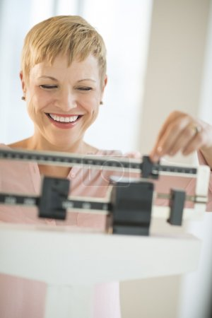 Cheerful Woman Using Balance Weight Scale