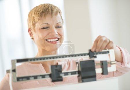 Photo pour Bonne femme mature ajustement balance balance de poids au club de santé - image libre de droit