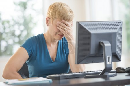 Photo for Tired mature businesswoman with hands on face leaning on computer desk in office - Royalty Free Image